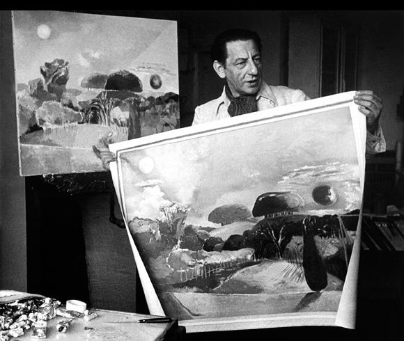 Paul Nash holding up two paintings of Wittenham Clumps in his studio